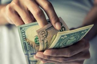 お札の金額を手で数えて確認している人