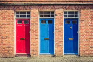 左から赤・水色・青のドアが並んでいる