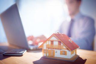 家の模型とノートパソコンを使って仕事をする人