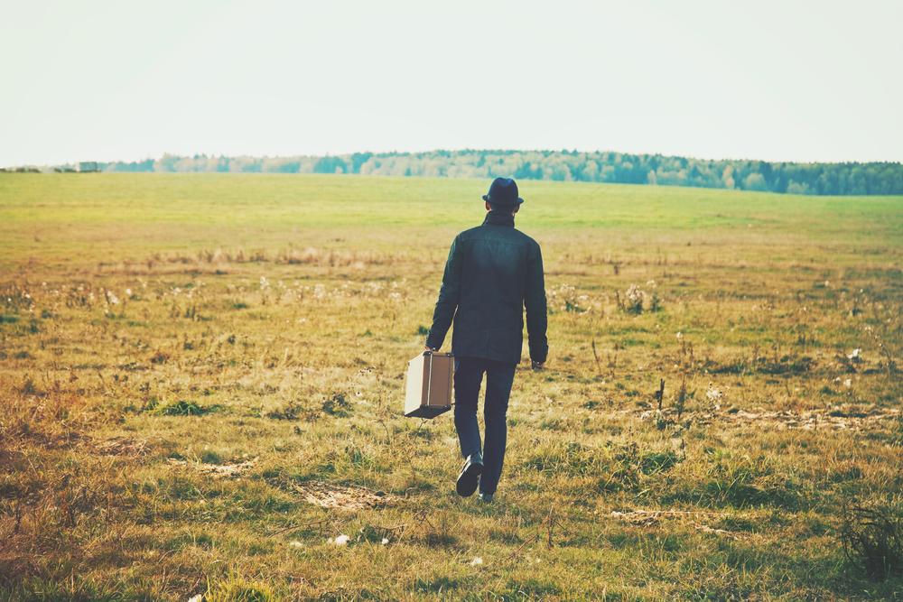スーツケースを持ってどこまでも広がる草原を歩く男性