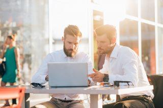 一つのノートパソコンを見ながら話し合う男性2人