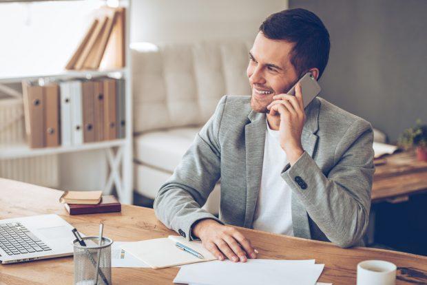 仕事中にスマートフォンで通話する笑顔の男性