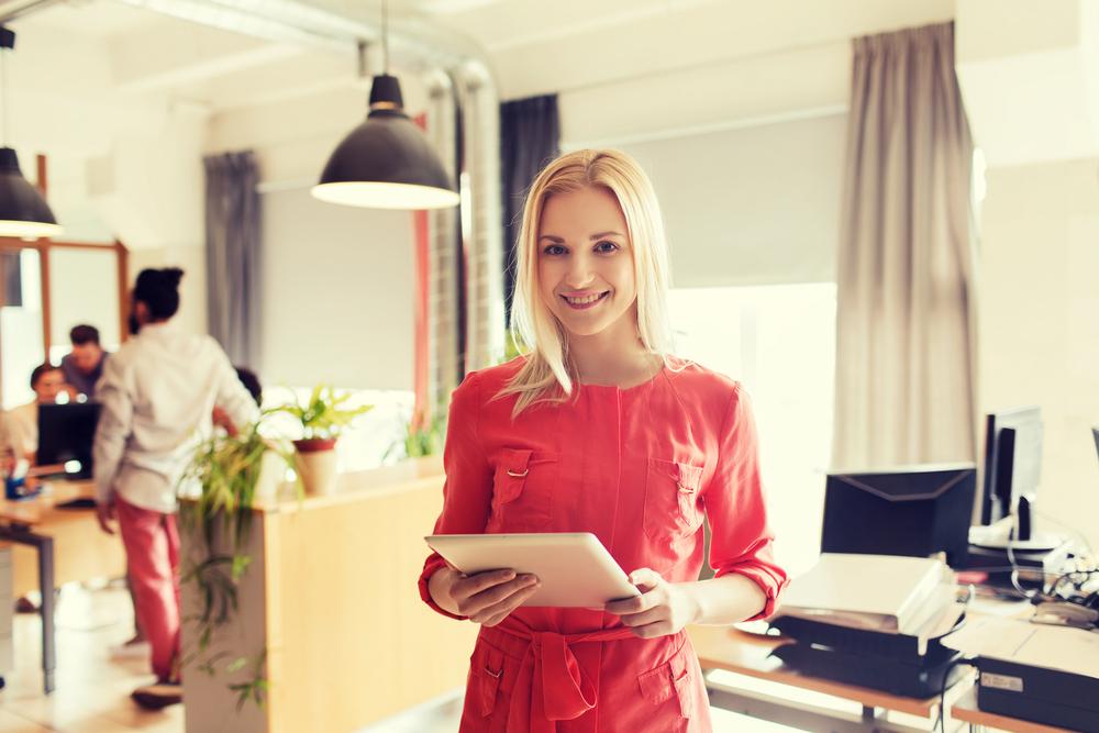 タブレット端末を手にして微笑む赤い服を着た女性