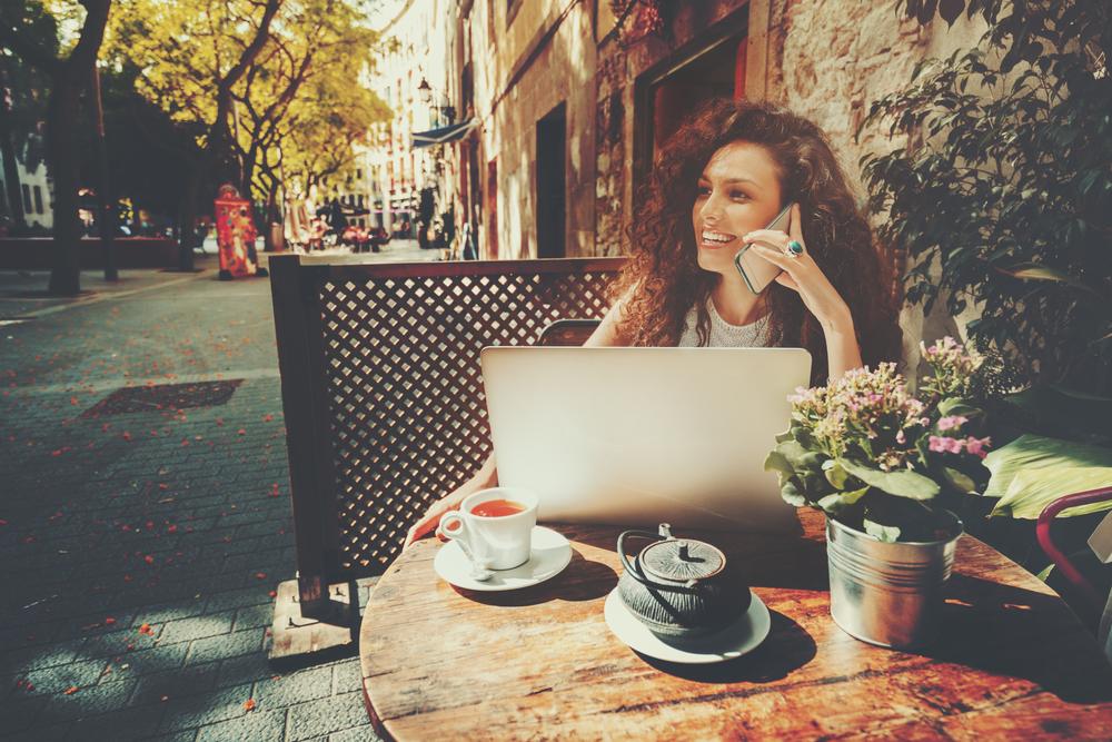 オープンカフェで仕事をしている笑顔の女性