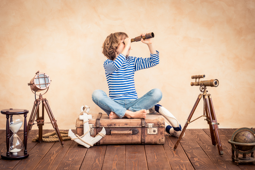スーツケースの上にあぐらをかいて望遠鏡で遠くを見る少年
