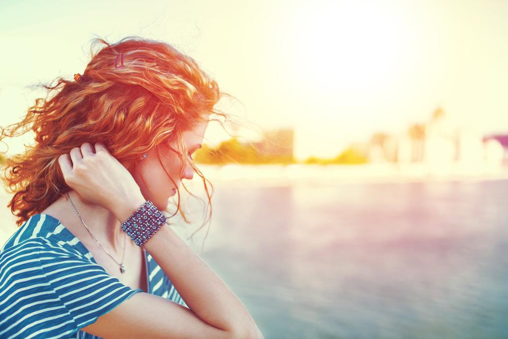 水辺でうつむき髪を触る女性