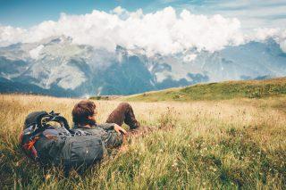 草原で寝そべるバックパッカー