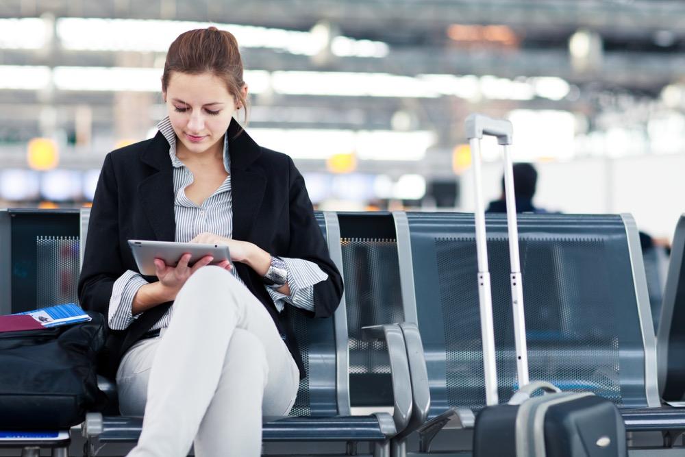 駅のホームで椅子に座り、タブレット端末を操作する女性