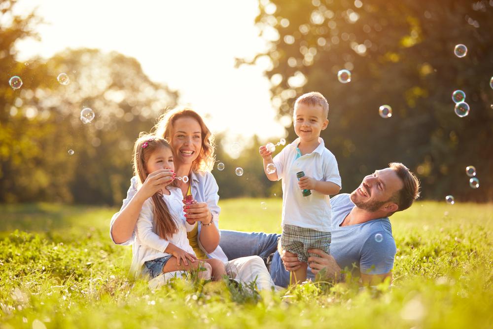 芝生の上で笑いながらシャボン玉を飛ばす家族
