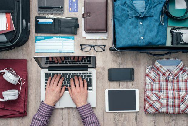 地方から出てくるために準備されたスーツケースとパソコンなどの端末