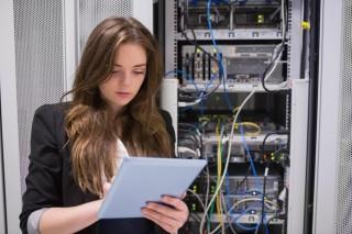 サーバールームでタブレット端末を操作する女性