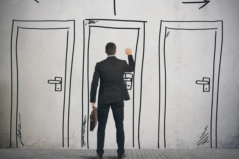 ドアをノックする黒いスーツの男性