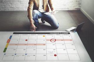 床に置かれた巨大なカレンダーにスケジュールを書き込む男性