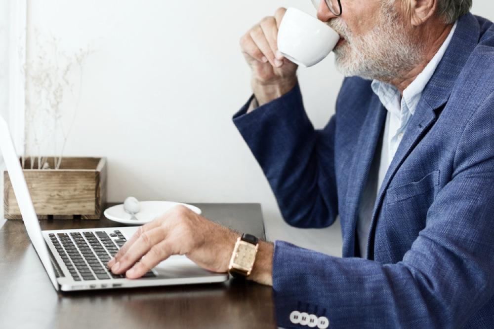 コーヒーを飲みながらノートパソコンを操作する年配の男性