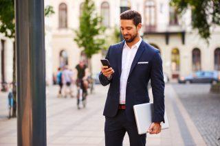 スマートフォンを見る紺色のスーツを着た男性