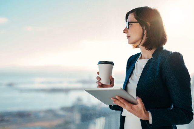 コーヒーを持って窓の外を眺めるスーツ姿の女性