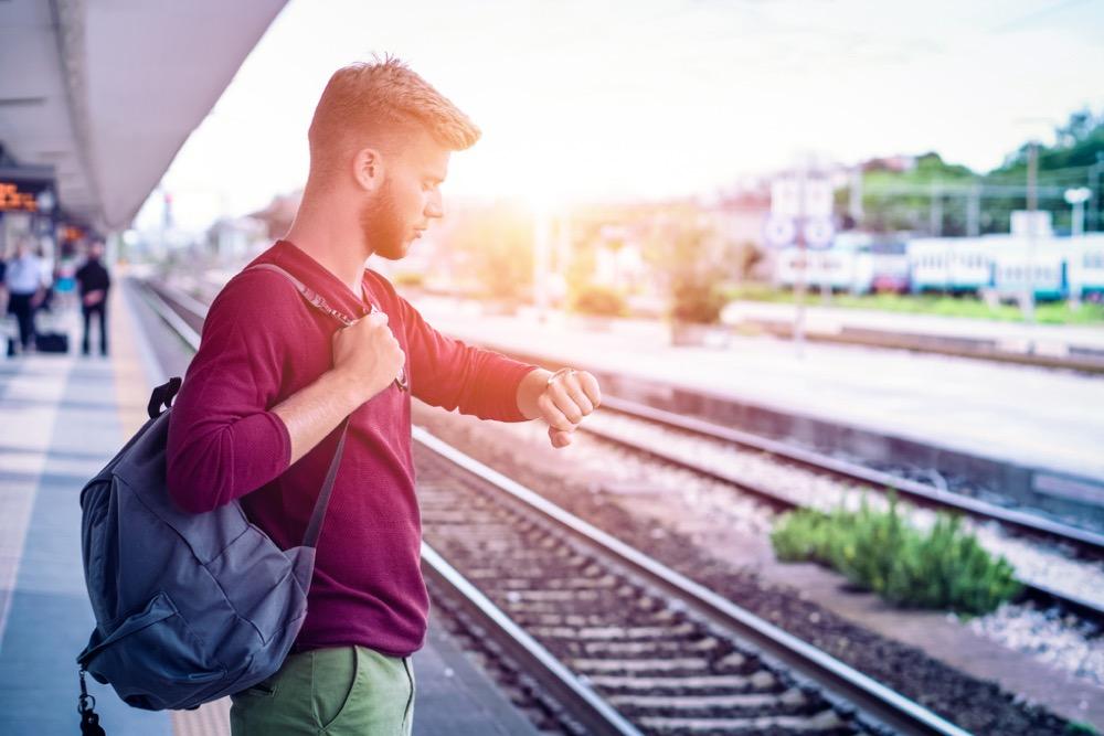 駅のホームで腕時計を見ながら電車を待つ男性
