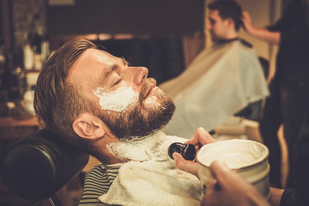 髭を剃って身だしなみを整える男性