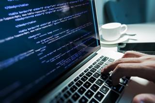 パソコンにコードを打ち込むプログラマー
