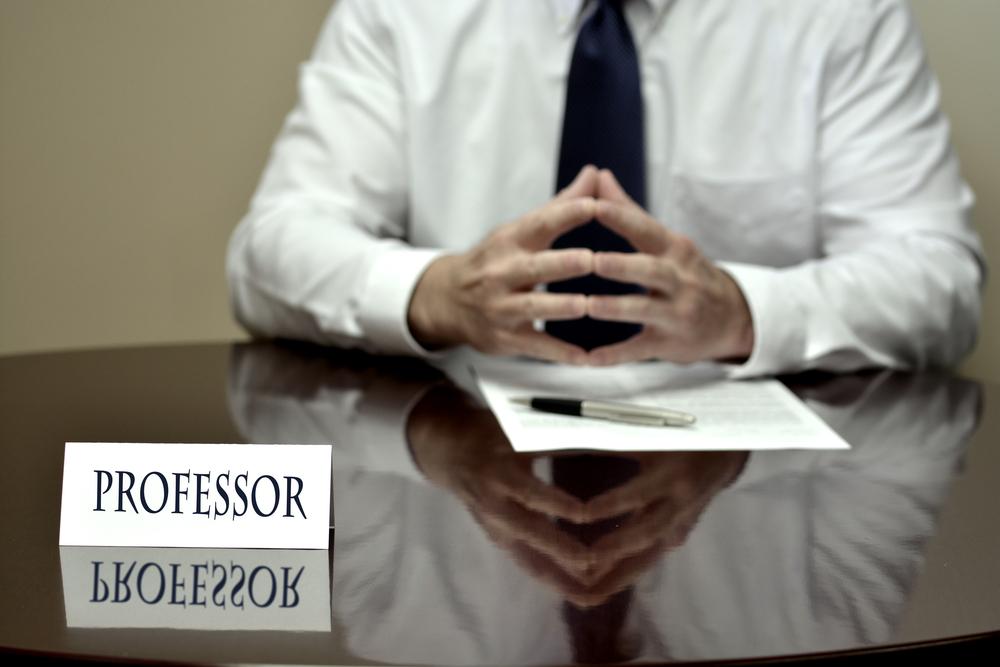 テーブルに手をのせる大学教授