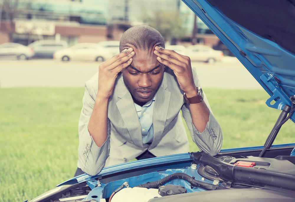 車が故障して頭を抱える男性