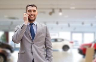 スマートフォンで通話するグレーのスーツを着た男性