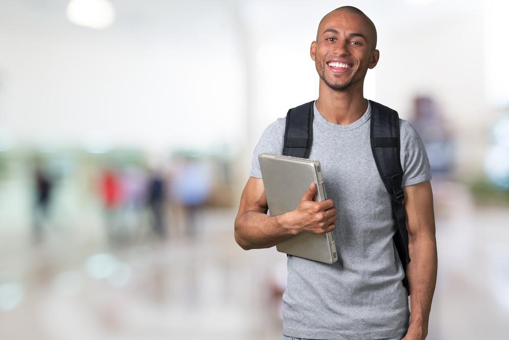 パソコンを片手に持つ学生