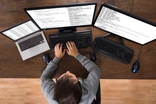 3つのパソコンを使いながら作業するプログラマー