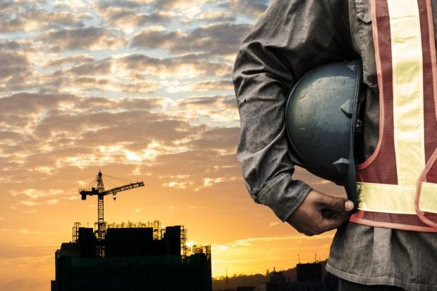 工事現場を背景に立つ作業員