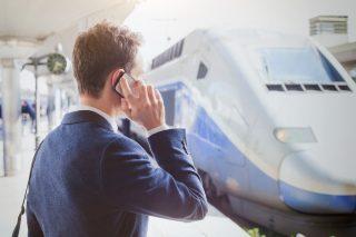 高速鉄道のホームで電話するスーツの男性