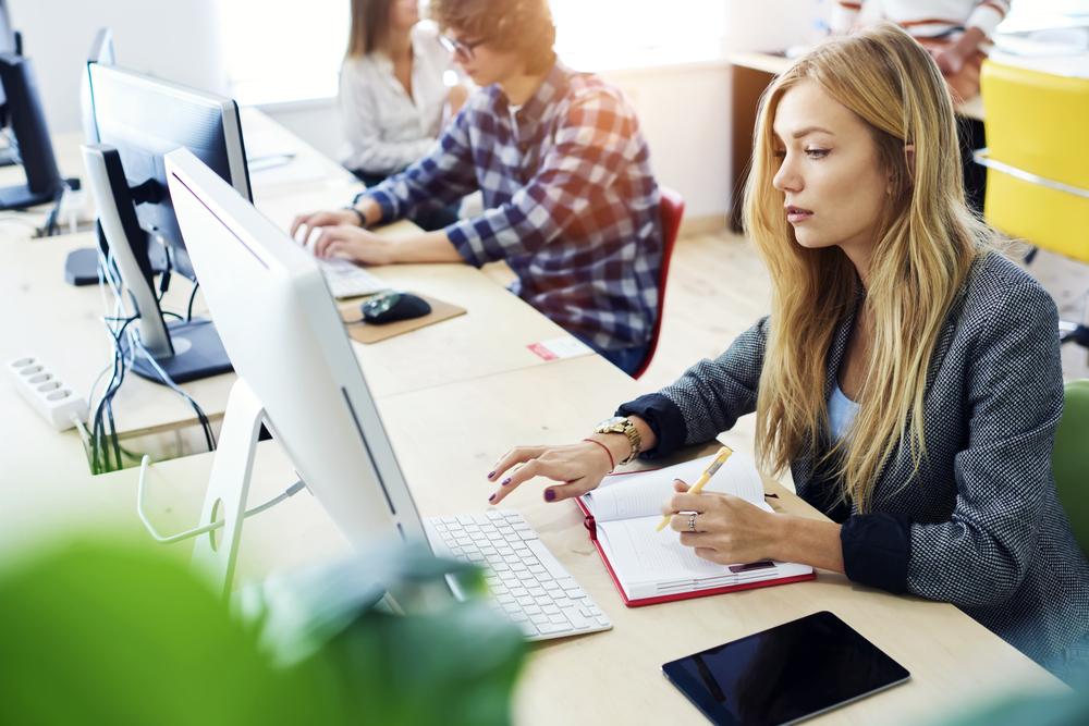 メモを取りながらパソコンを操作する女性