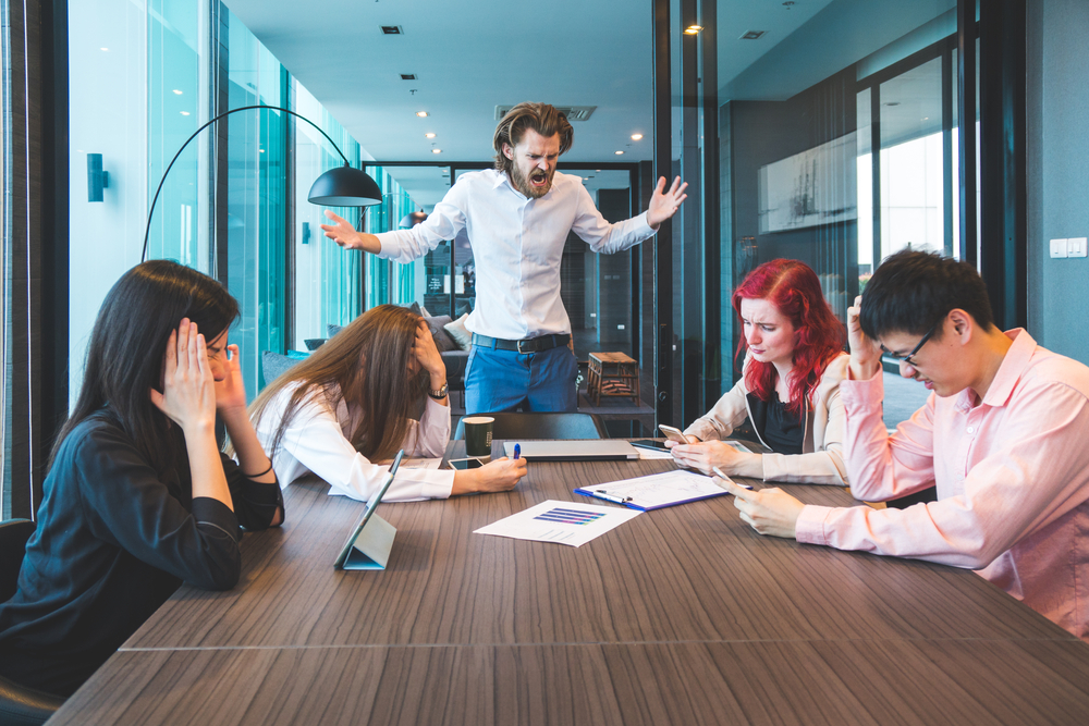 会議中に怒鳴っている男性と、頭を抱える他のスタッフ