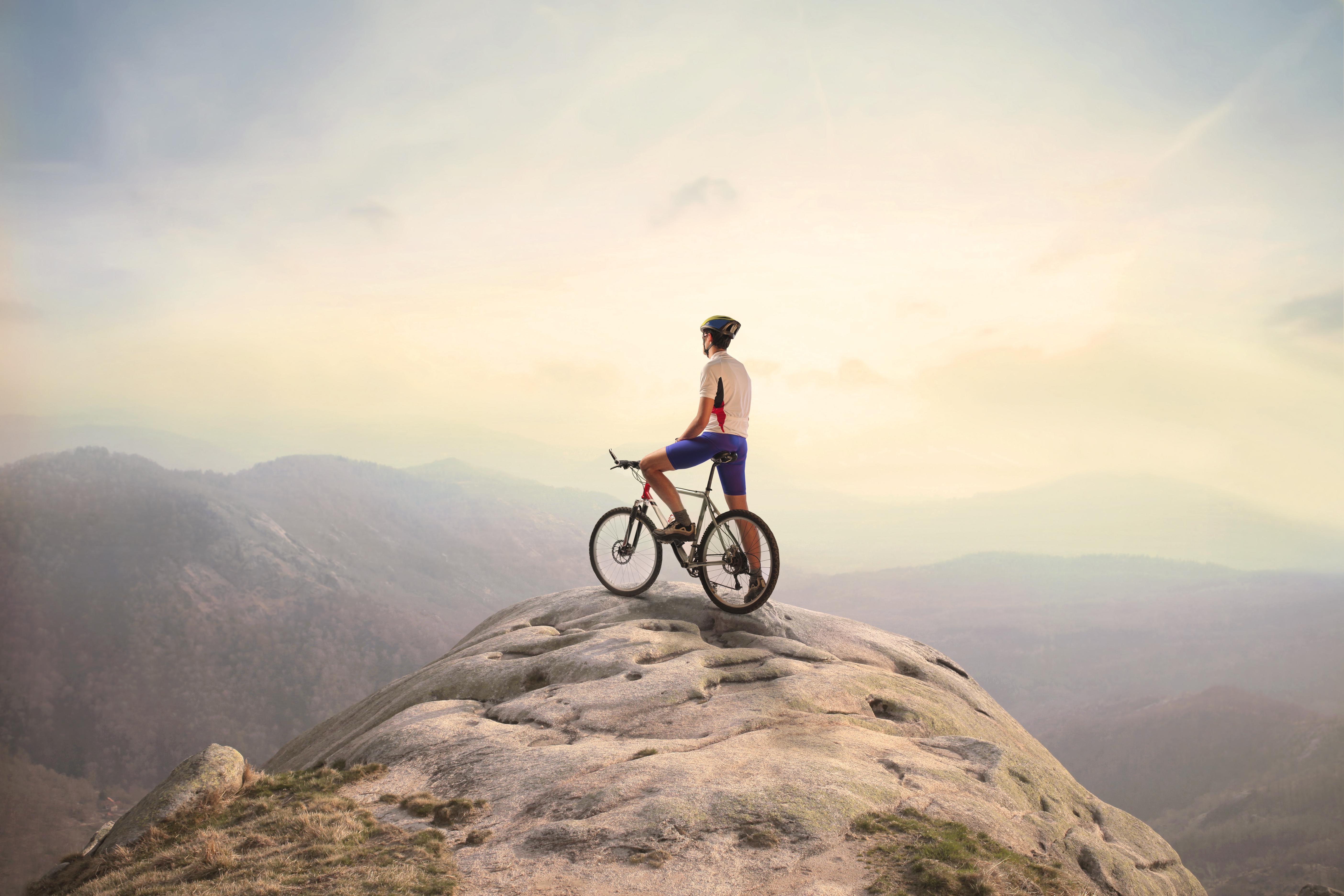 自転車にまたがり山頂から遠くを眺める男性
