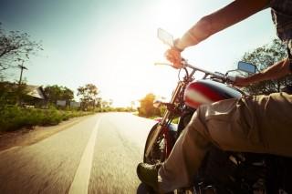 バイクにまたがりツーリングする人