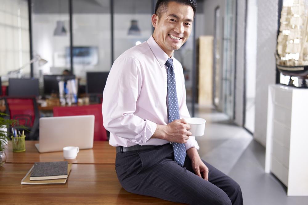 オフィスのデスクでリラックスしてコーヒーを飲むビジネスマン