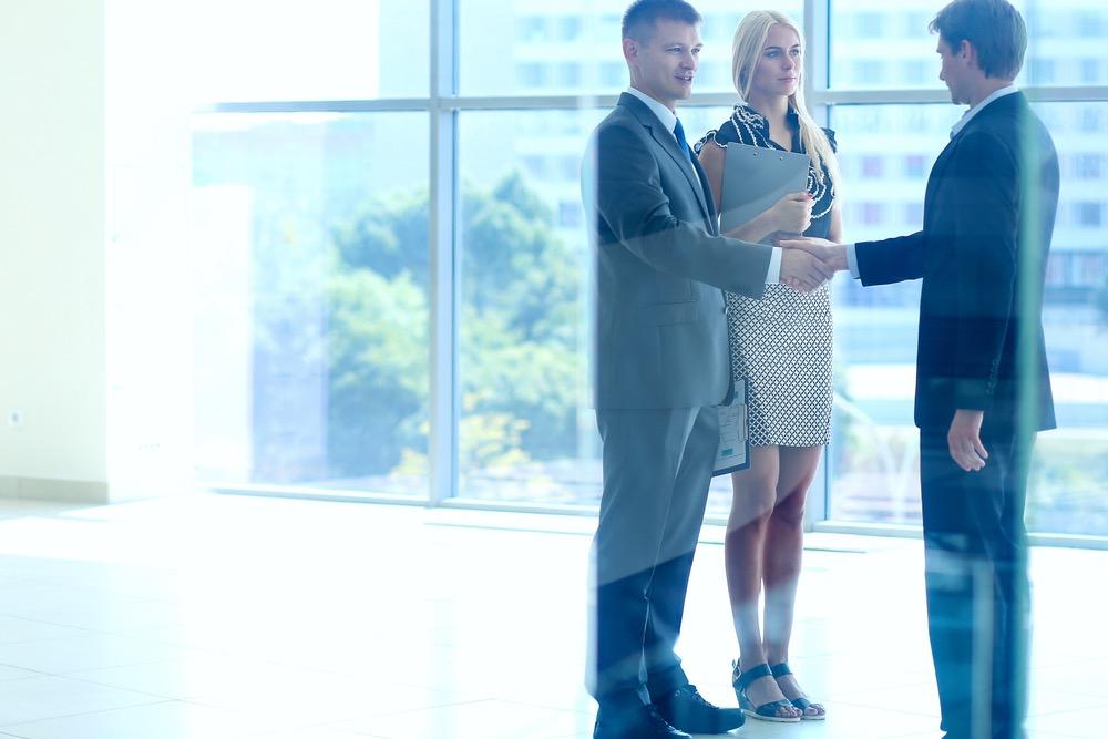 握手するスーツの男性と女性秘書
