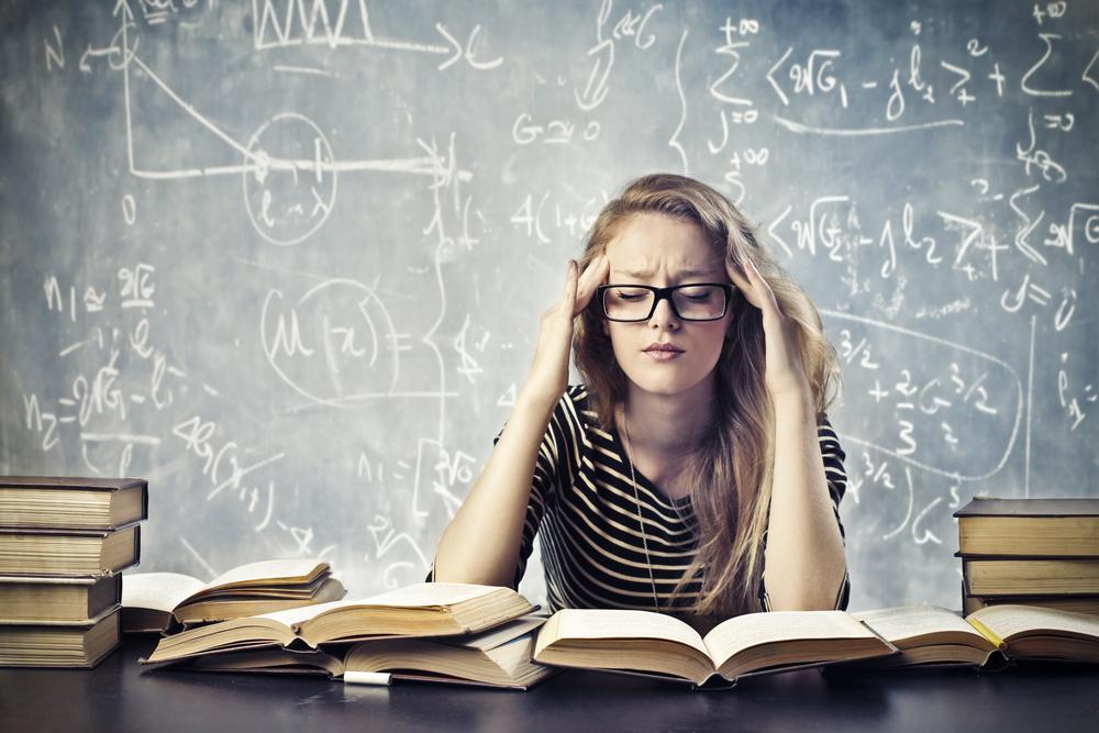 数式の書かれた黒板の前に座り、こめかみを抑えて悩む女性