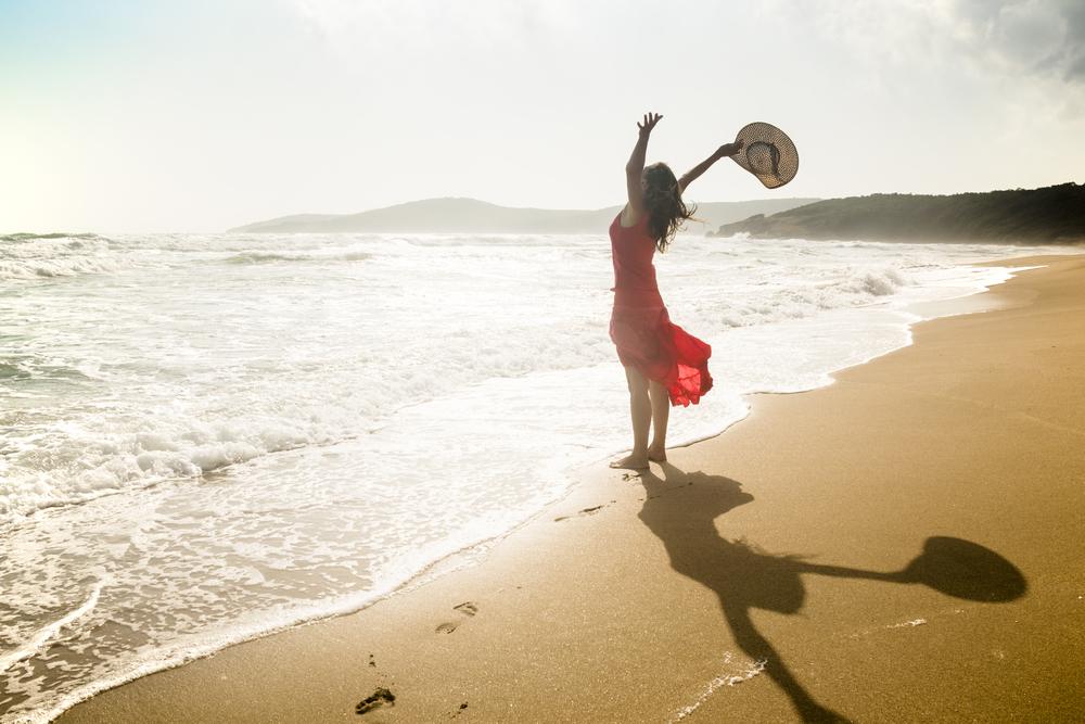 波打ち際で両手を大きく広げる赤いワンピースの女性