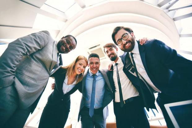 笑顔で肩を組むスーツを着た人々