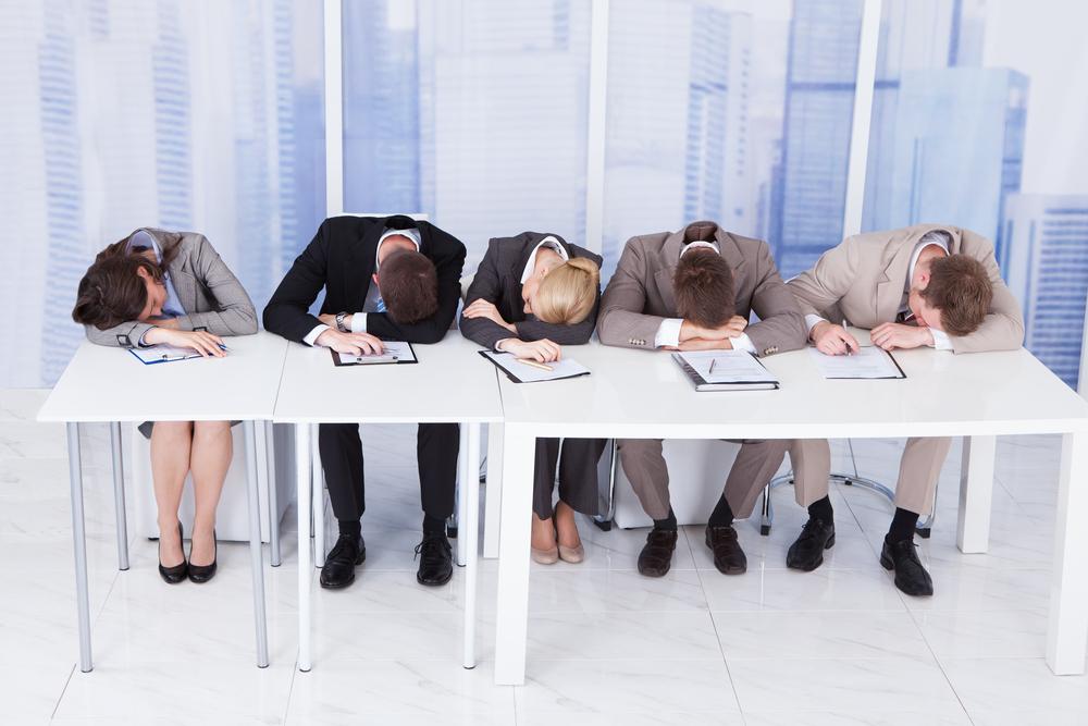 デスクの上で居眠りしているスーツを着た男女