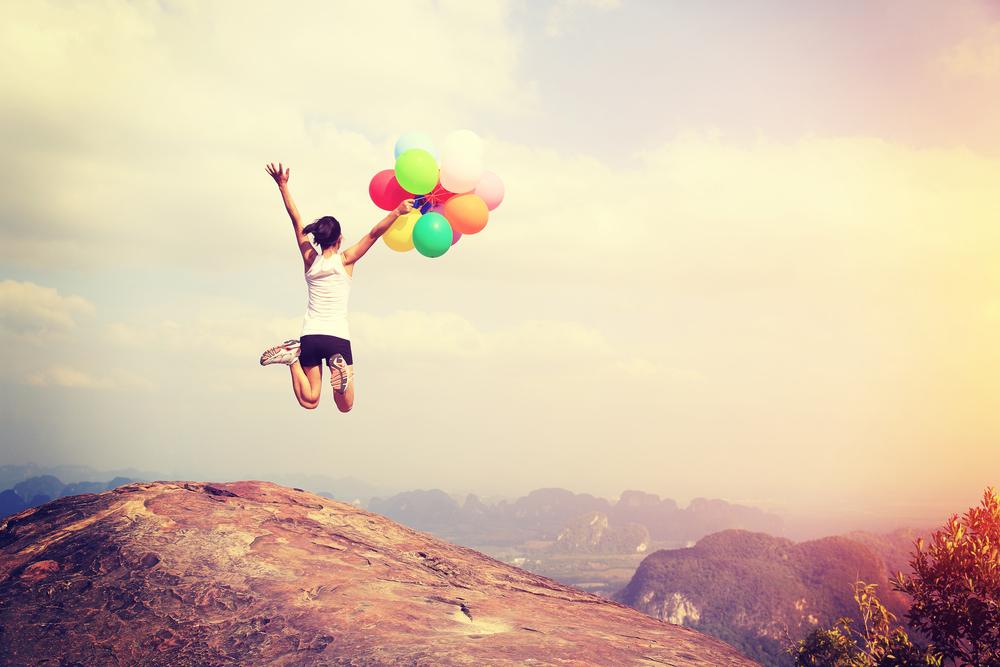 風船を持って山頂をジャンプする人