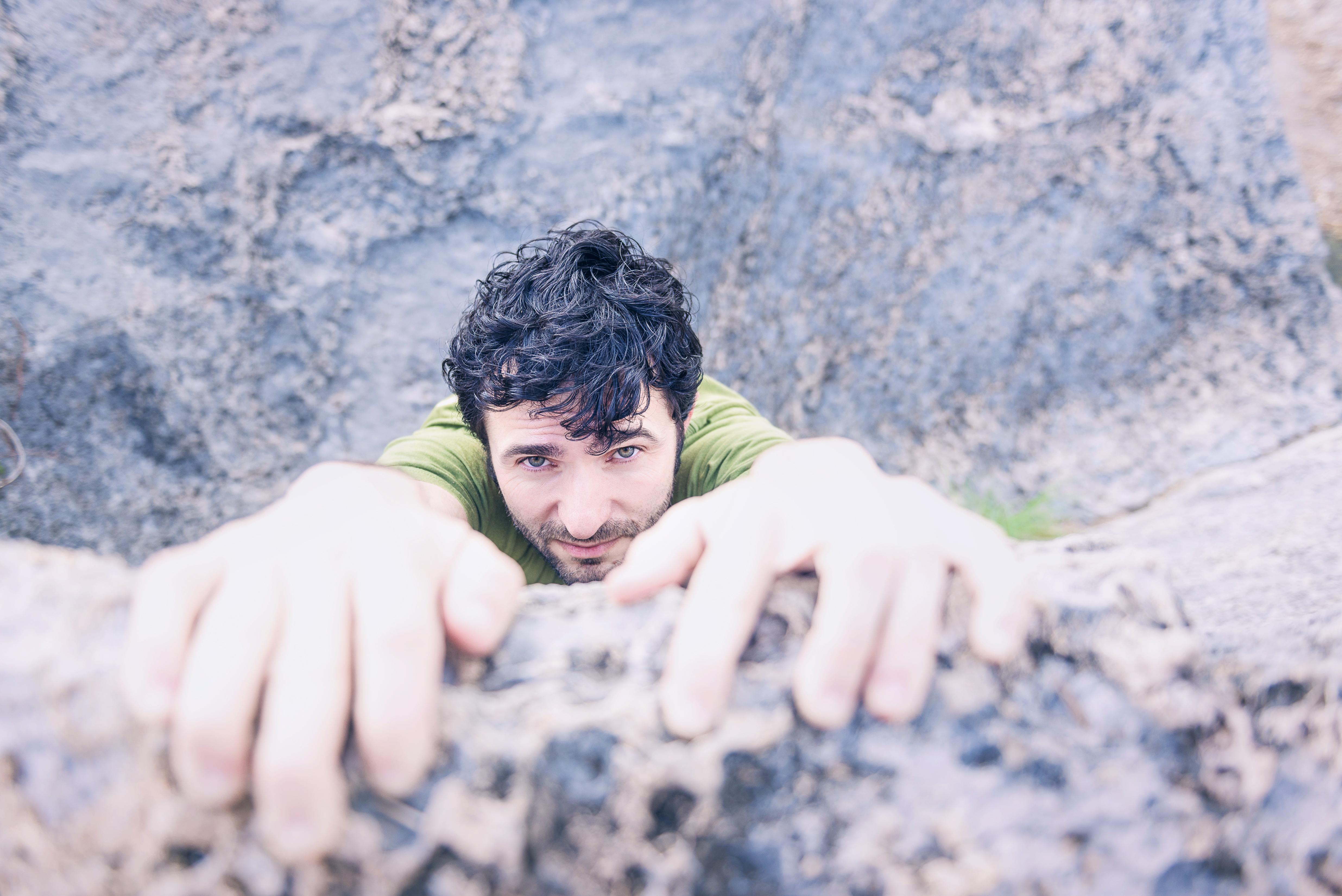 落ちそうになりながら崖っぷちにしがみつく男性