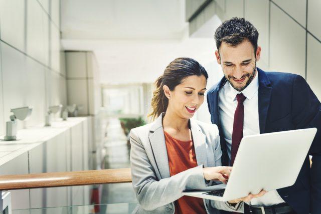 オフィスの中でノートパソコンを開いて会話する男女