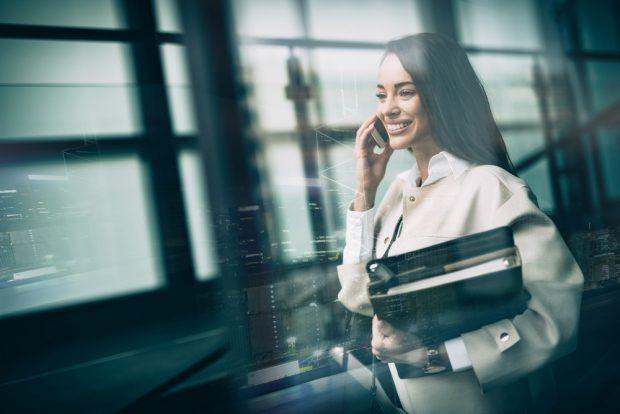 分厚い資料を脇に抱えながら、笑顔で電話する白いスーツの女性