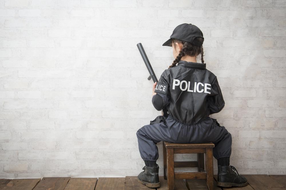 背中に「POLICE(警察官)」と書かれたツナギを着て椅子に座る少女