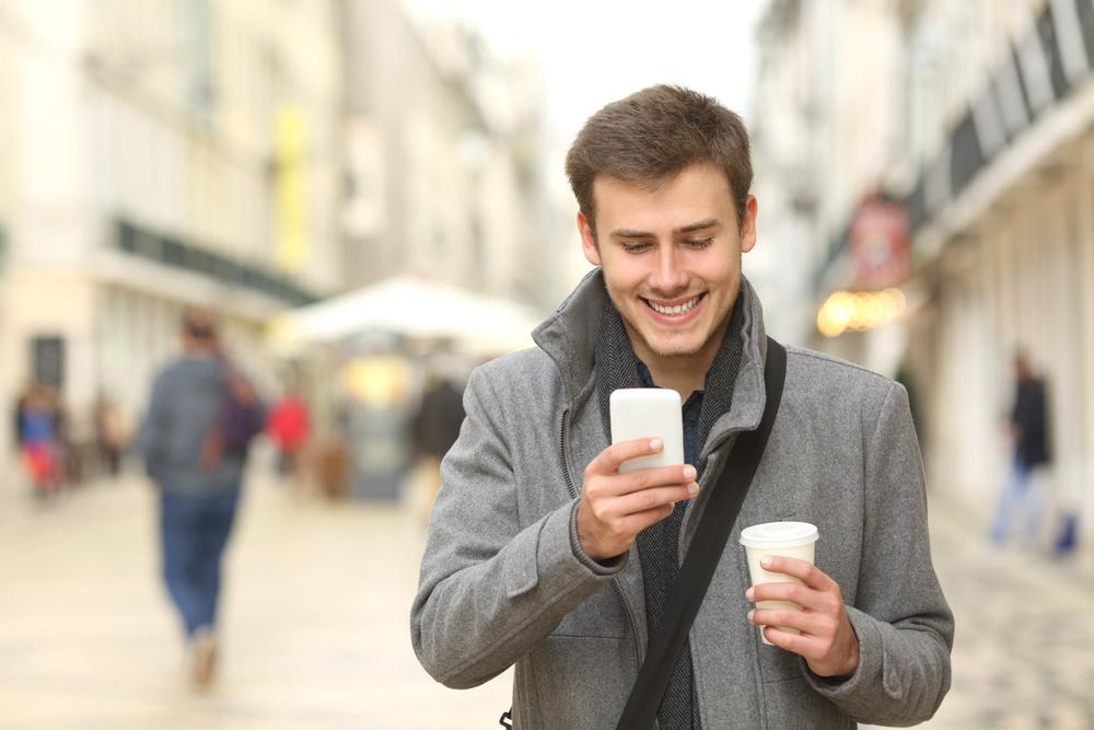 スマートフォンを見て微笑む男性