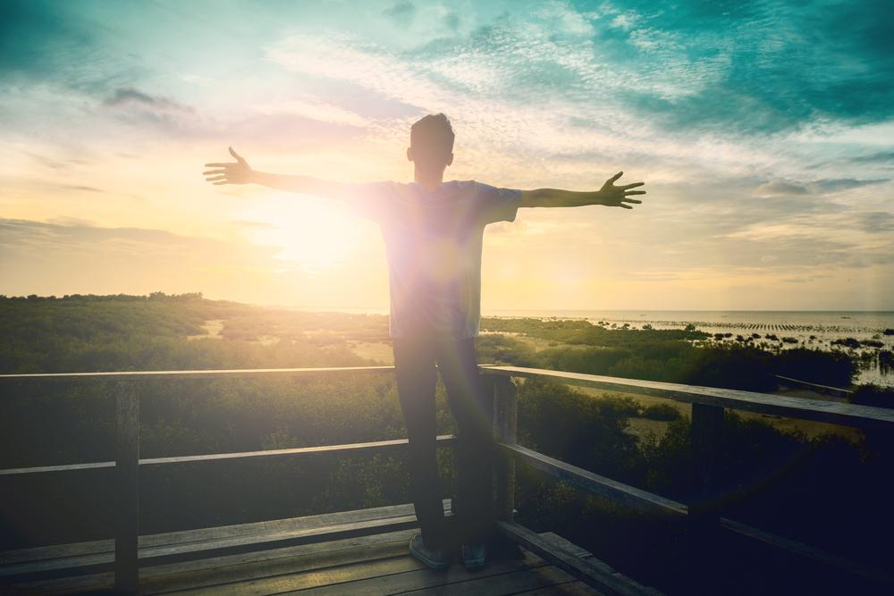 朝日に向かって手を広げる男性のシルエット