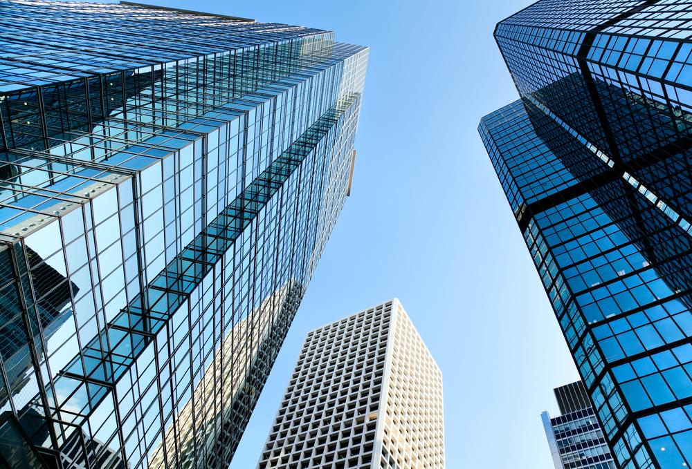 青空の下に建つオフィスビル街