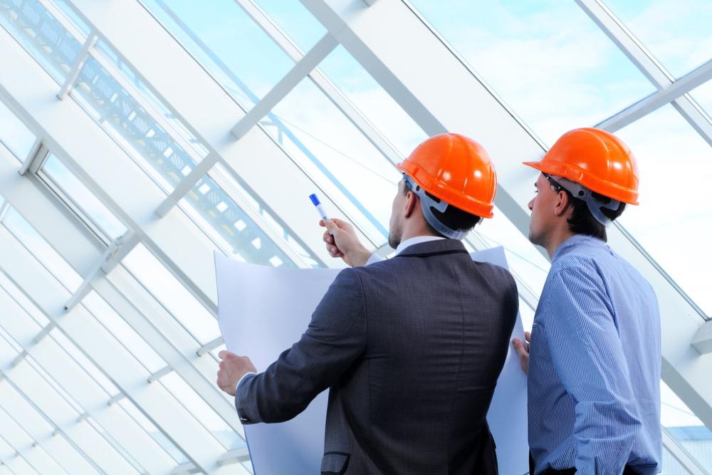 設計図と照らし合わせて工事中の建物を確認する現場監督