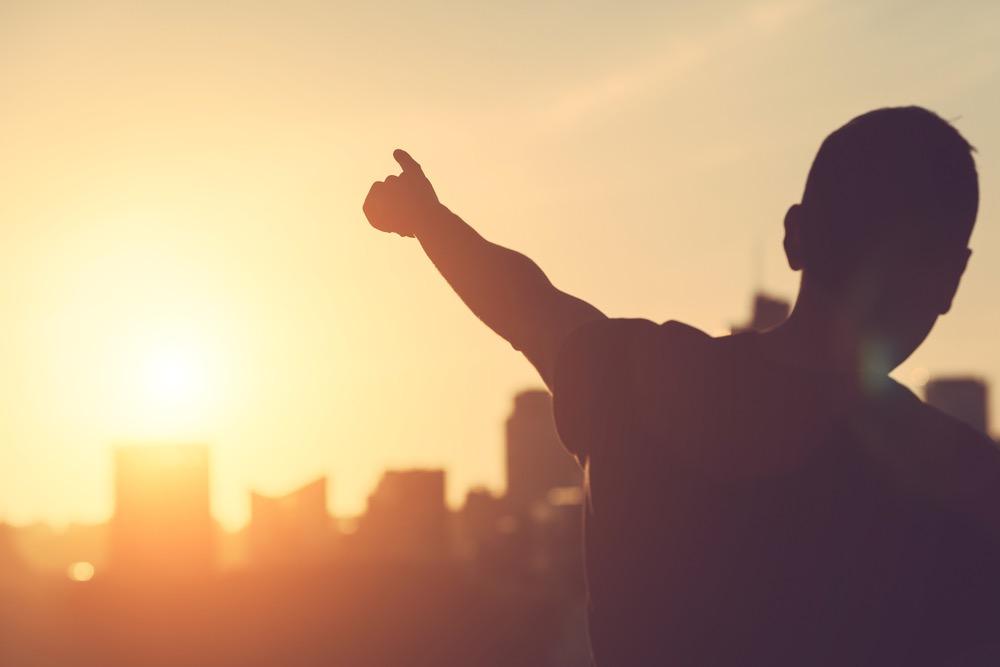 夕日を指さす男性